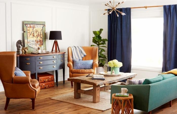 exemple de deco dejour campagne chic, parquet clair, fauteuils en cuir, canapé leu canard, table basse en bois rustique, rideaux bleu marine, meuble de rangement retro et malles vinatge