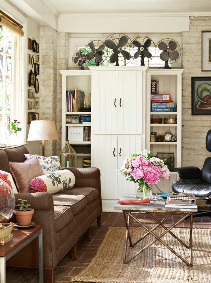 idée deco sejour campagne chic, bibliothèque avec des placards, canapé marron, table basse, mur en pierre, deco cadres, bouquet de fleurs
