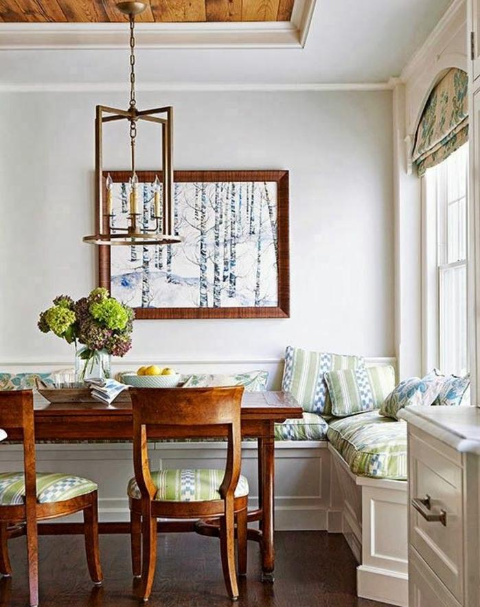 idée deco sejour campagne chic, table et chaises en bois rustique, canapé d angle, coussins en vert et bleu, suspension vintage, tableau decoratif, forêt nordique
