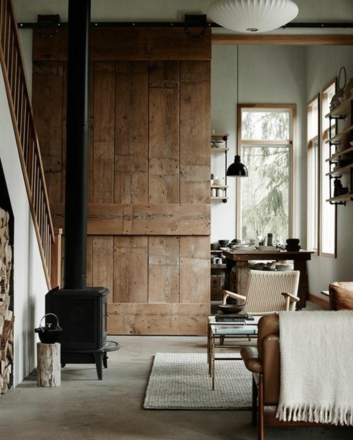 deco sejour campagne chic, cheminée rustique, rev6etement sol en béton, canapé en cuir marron, table basse, buche de bois, porte en planches de bois, salle à manger