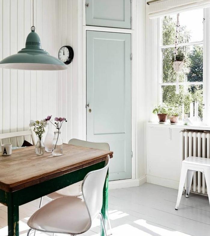 exemple deco campagne salle à manger, table en bois et métal, chaises scandinaves, parquet blanchi, suspension et porte vert pastel, decoration florale