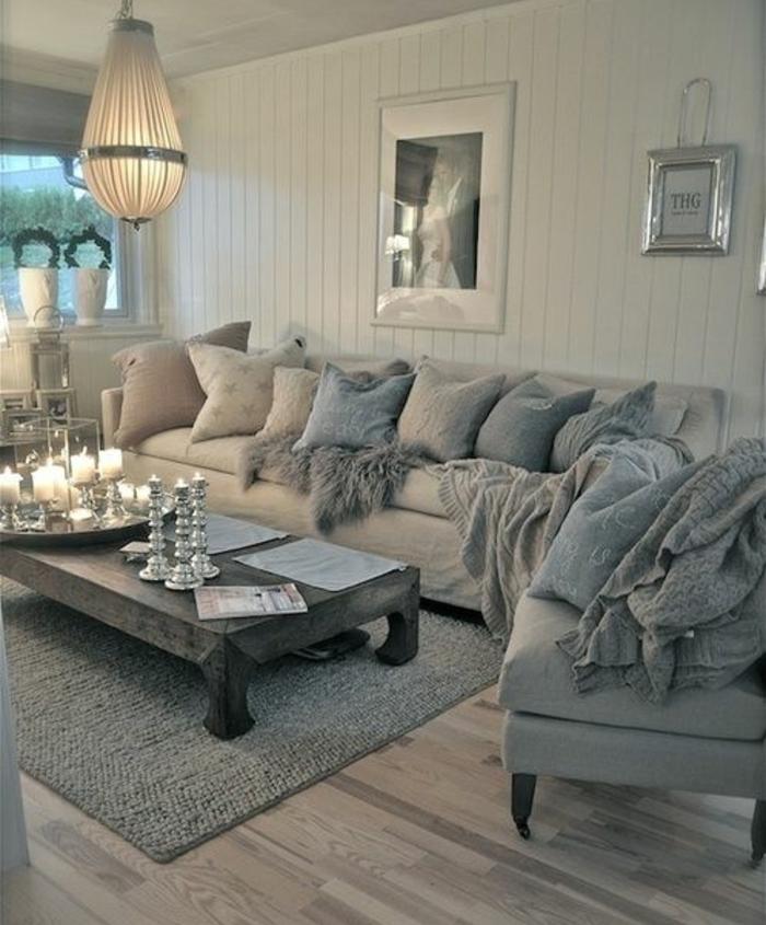 deco campagne chic, parquet en bois, canapé et fauteuil gris, suspension originale, table basse en bois grise, coussins bleu, blanc et gris, chandeliers et bougies