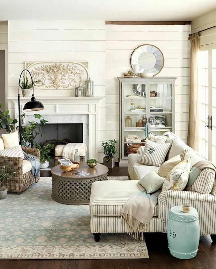 deco style rustique, tapis à motifs floraux, canapé à rayures et fauteuil en rotin, table basse ronde style oriental, cheminée, buffet blanc vintage, parquet marron, deco campagne chic