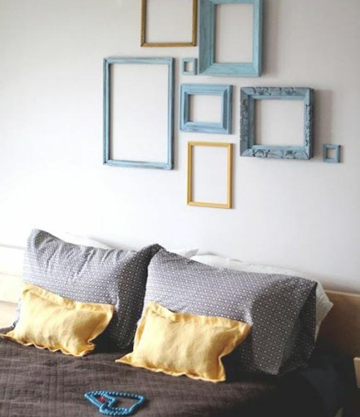 idee comment décorer une chambre a coucher design, mur de cadres bleus et jaunes, lit en bois, couverture de lit gris et jaune
