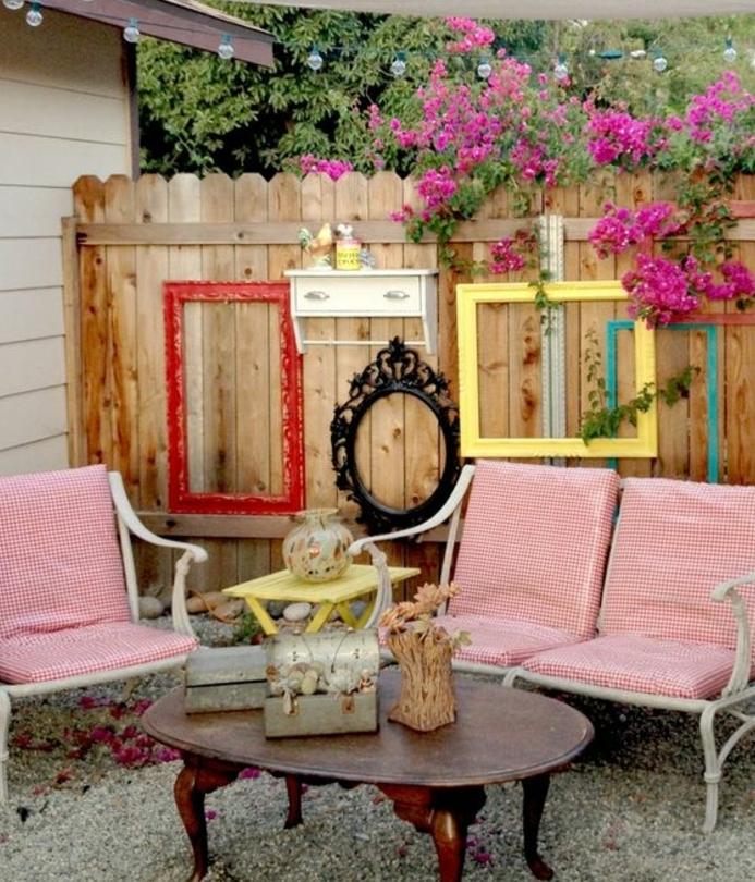 palissade de planche en bois, décorée de cadres vides vintage forme ovale et rectangulaire et couleurs divers, fleurs, chaises en metal blanches et coussins de chaise en blanc et rouge, idee deco exterieur