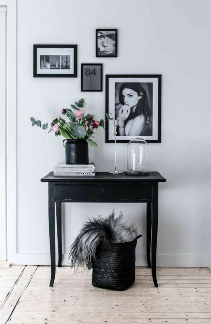 amenagement hall d'entrée maison décoré avec des tableaux aux cadres noirs et table classique noir et panier de rangement en noir