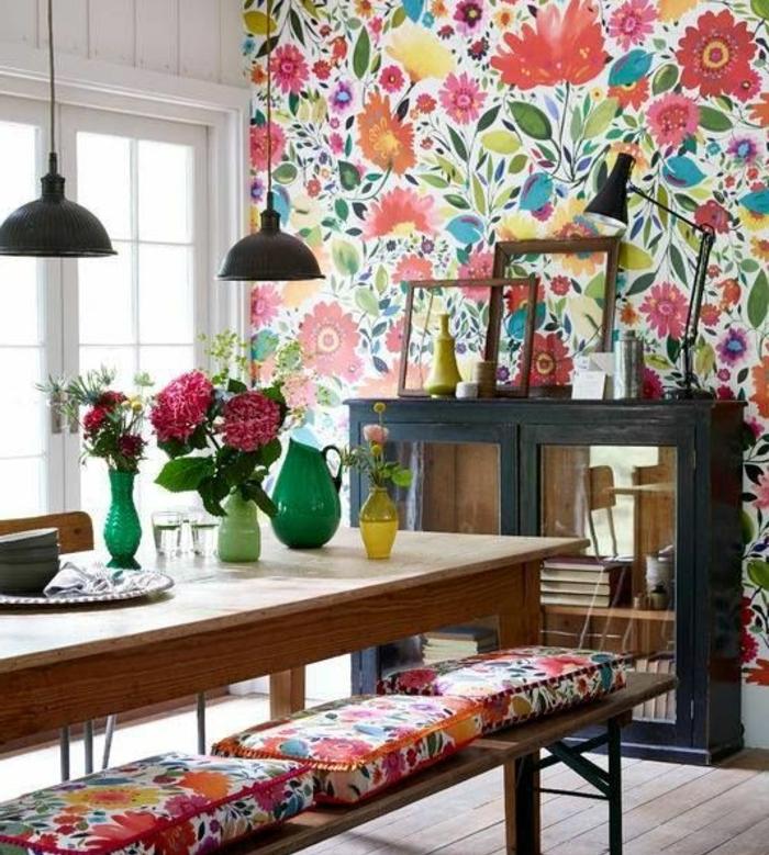 une cuisine campagne chic, mur d accent, papier peint floral, vaisselier en bois et verre, table salle à manger en bois, bancs avec coussins multicolores, deux cadres vides, deco cadre vide