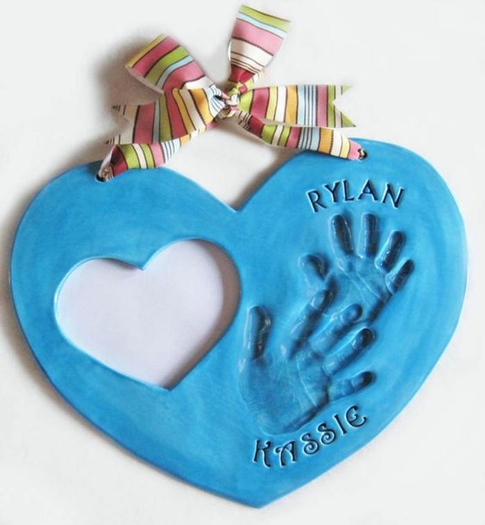 empreintes de mains bébé, idee cadeau fete des peres bebe, pâte bleue en forme de coeur et ruban multicolore, un trou en forme de coeur