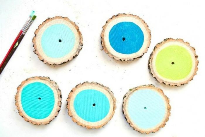 des rondelles de bois repeintes de couleurs diverses et transformés en sous verres customisés, activite manuelle idee inéressante