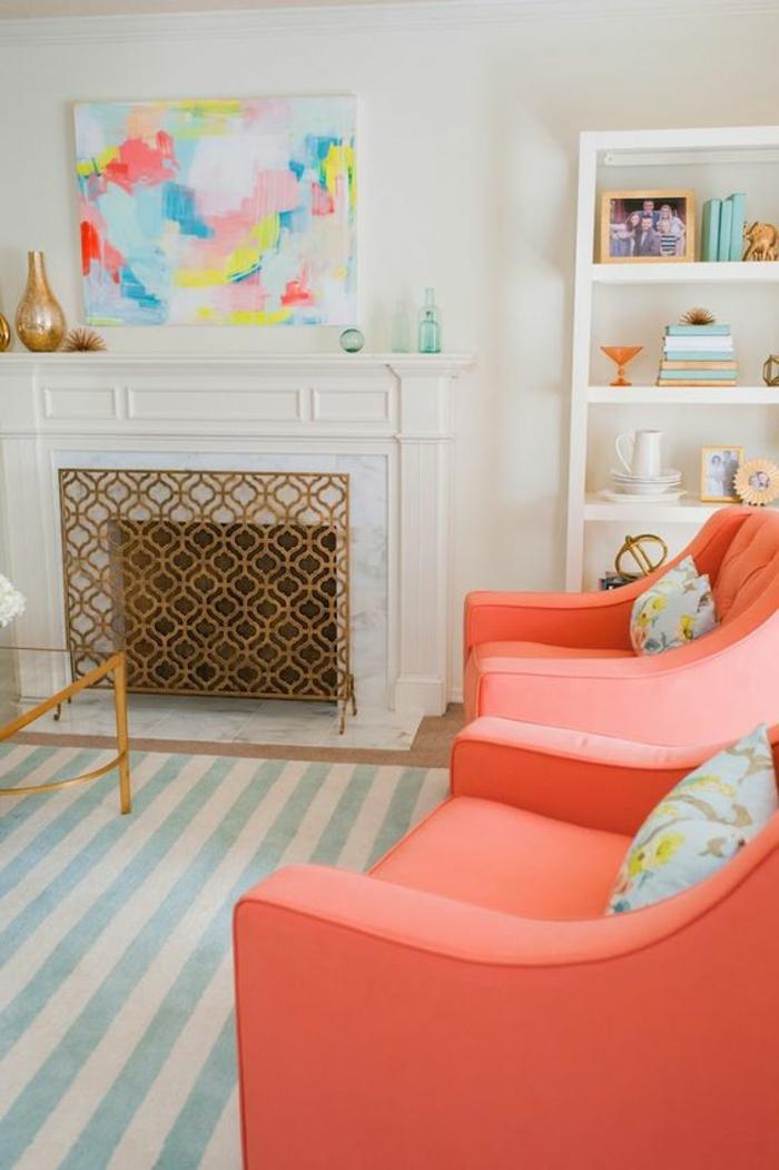 deux fauteuils roses et cheminée décorative, bibliothèque intégrée, tapis à rayures