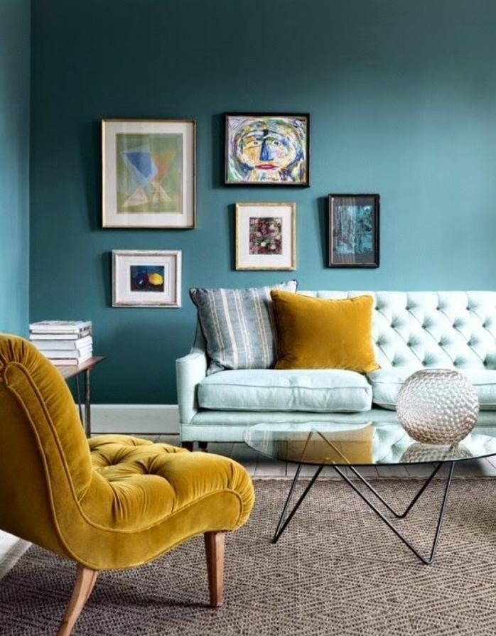 idee deco bleu canard couleur peinture, fauteuil et coussin jaune, tapis bleu clair, tapis marron, table basse en bois et métal, decoration murale tableaux abstraits