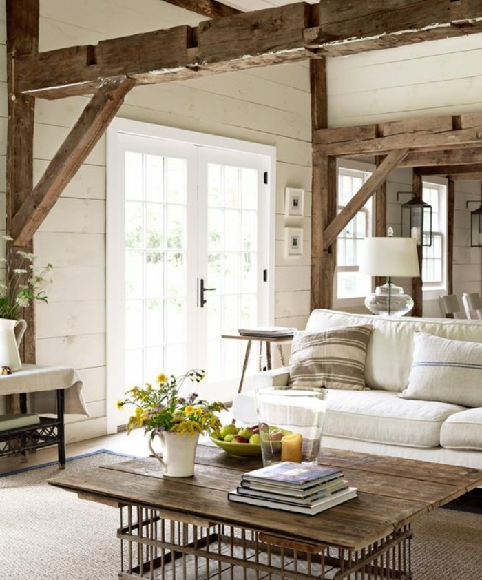 deco campagne chique rustique, poutre apparente, canapé blanc, coussins decoratifs, tapis marron, table recup en planche de bois et pieds en cagette métallique