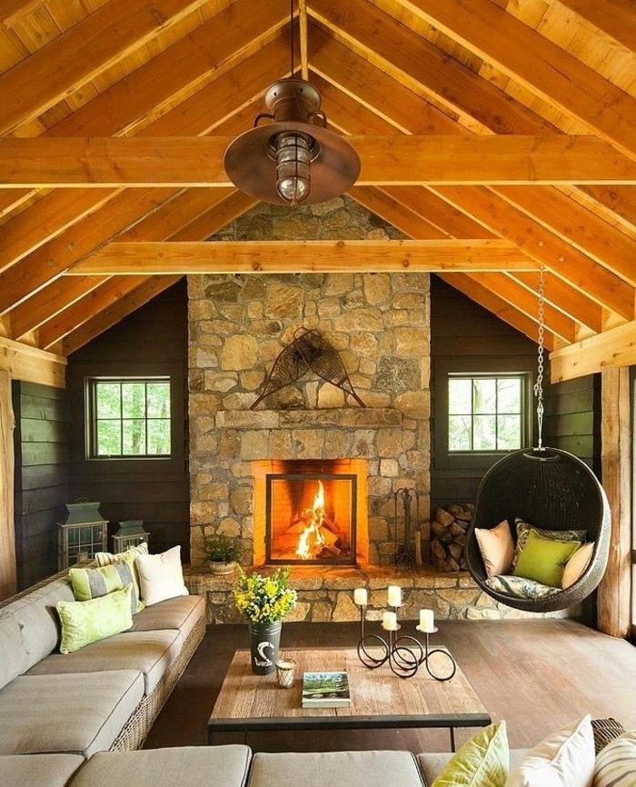 cheminée en pierre, balançoire suspendue, table en bois et métal, canapé gris long, chandelier, maison ossature bois, toiture poutre apparente
