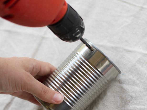 tutoriel premier étape pour créer un rangement ustensiles de cuisine, percer un trou dans la boite de conserve pour y insérer le crochet de suspension, deco boite conserve