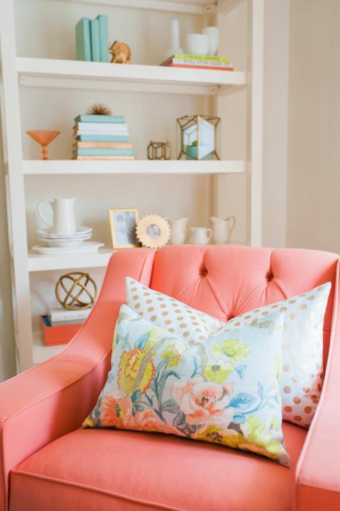 fauteuil rose saumon, étagère blanche, coussins déco motifs floraux, accessoires déco