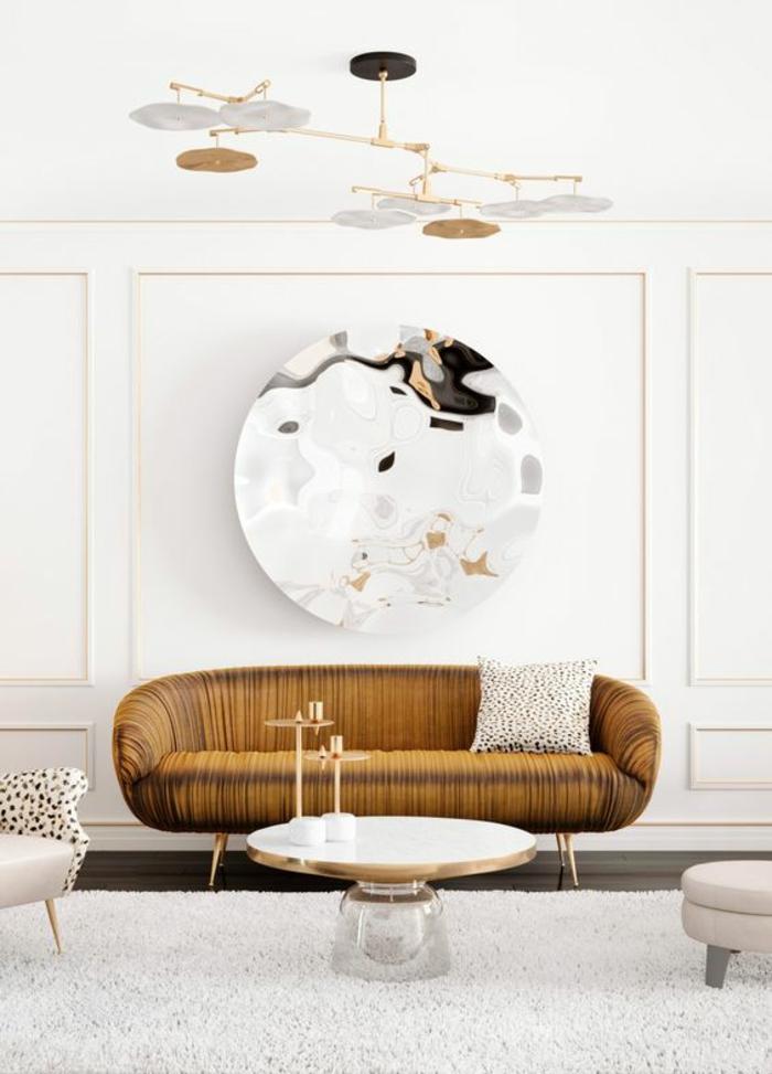 miroir sorcière grand rond sans cadre au dessus d un canapé en nuances du marron et des luminaires réflechis dans le miroir