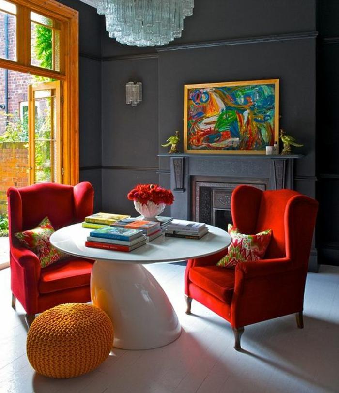 gris perle, table blanche avec des fauteuils en rouge vif, fenêtre orange, plafonnier en cristal, pouf tricoté