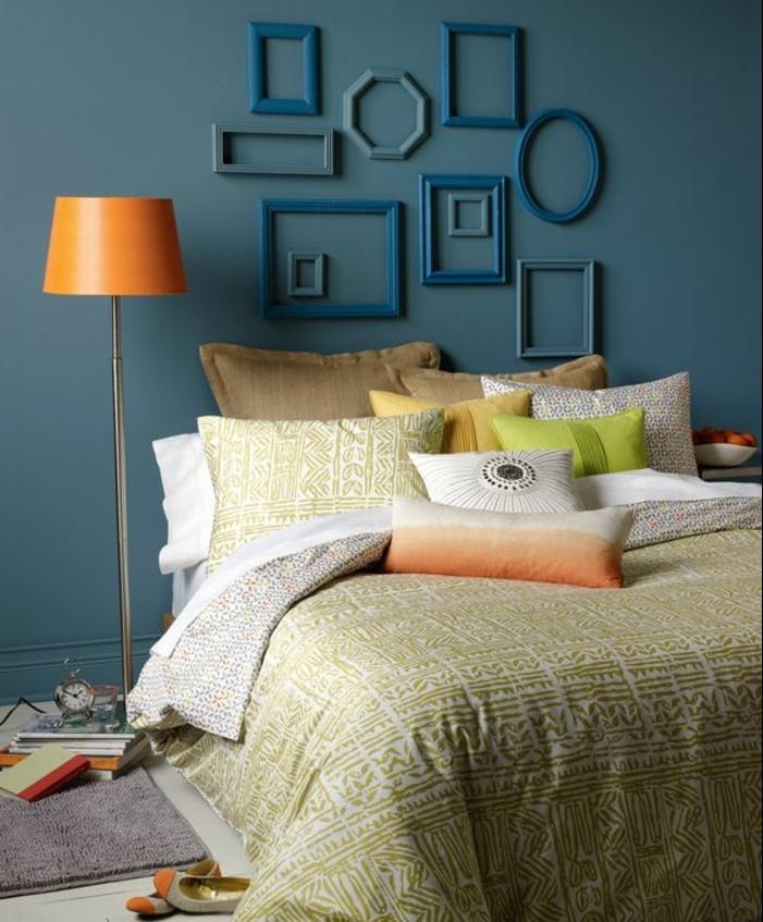 deco chambre a coucher murs couleurs bleu canard, couvertures de lit et coussins en blanc, vert, beige, marron et jaune, deco cadre vide, plusieurs cadres ovales, rectangulaires et carrés, lampe orange
