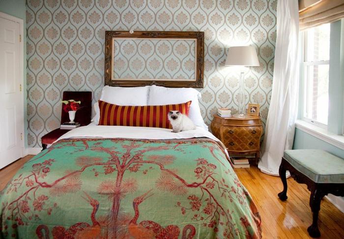 deco cadre vide en bois vintage, grand format, couverture de lit chinoiserie, linge de lit blanc, coussin en rouge et orange, papier peint à motifs floraux, parquet en bois clair, table de nuit retro