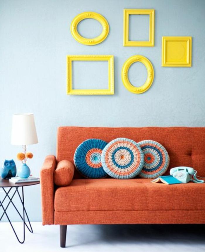 deco cadre vide avec des cadres jaunes ovales et rectangulaires, disposition asymétrique, canapé orange, table d appoint en bois et métal, lampe design