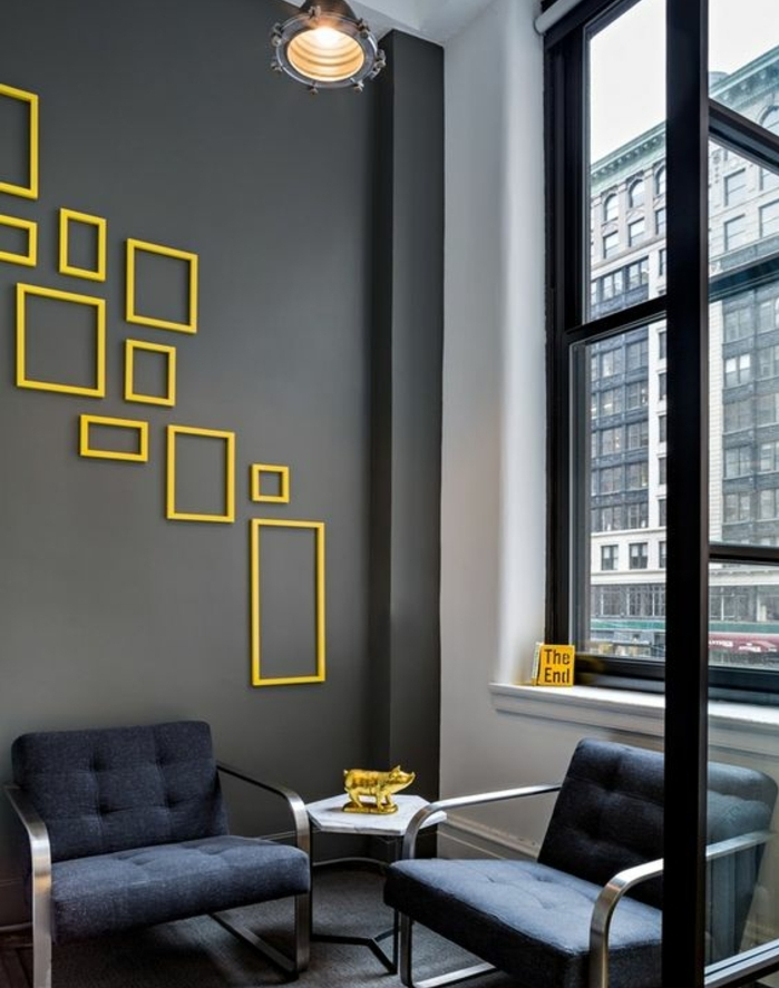 mur de cadres vides jaunes, format divers, couleur mur gris anthracite, fauteuil bleu foncé, decoration cochon doré, suspension industrielle
