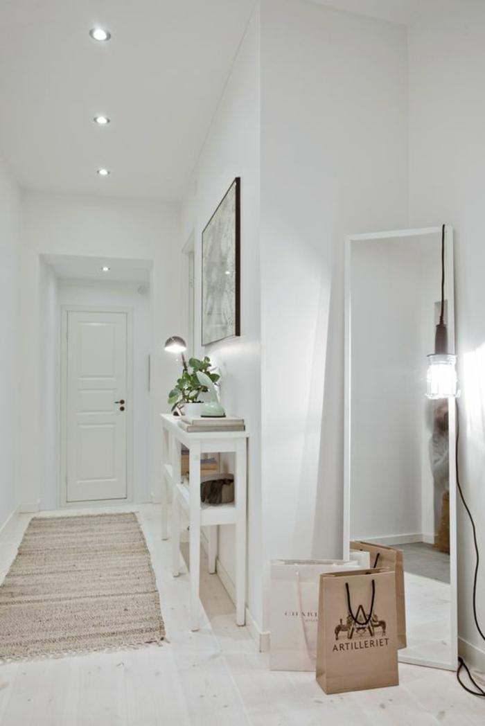 amenager hall d'entrée tout en blanc avec grand miroir appuyé au mur éclairé avec une grande ampoule design