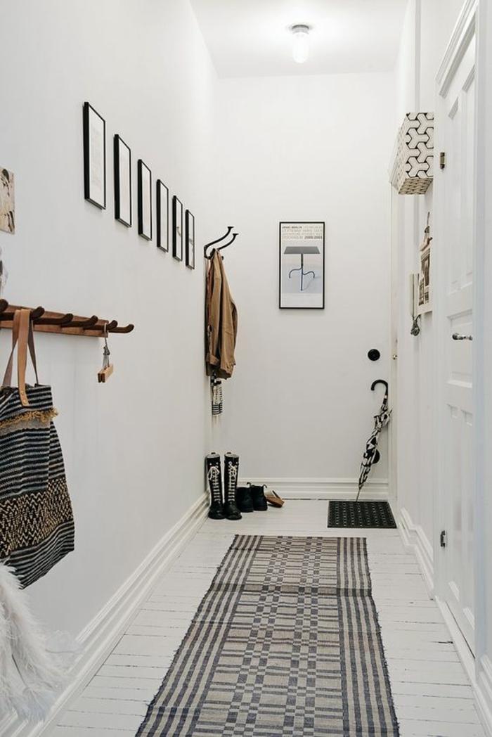 décoration hall d'entrée couloir long et étroit avec des tableaux aux cadres noirs et tapis en noir et blanc
