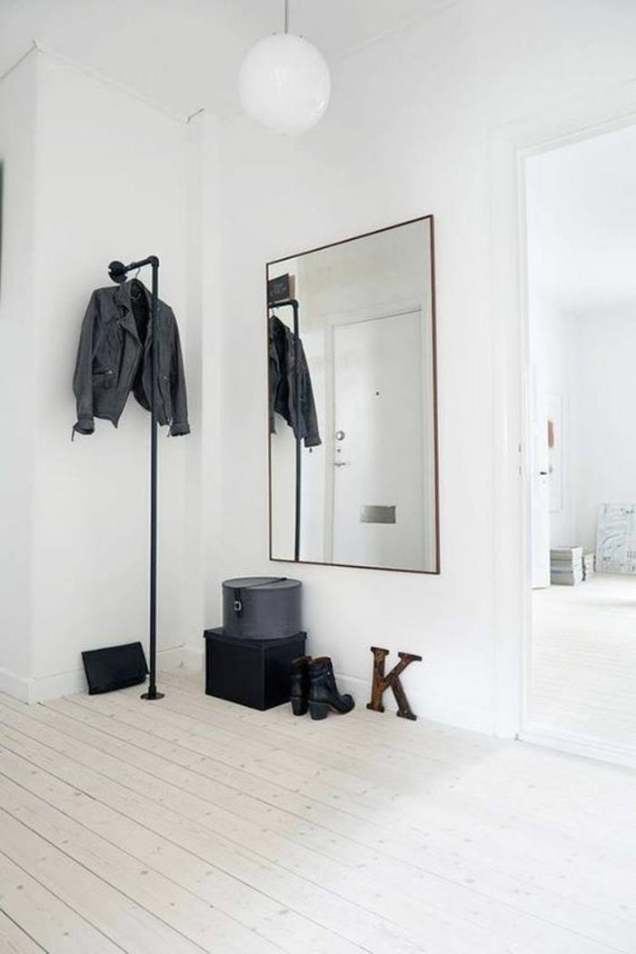 idée déco hall d'entrée spacieux avec grand miroir au cadre noir et suspension en métal noir pour les vestes