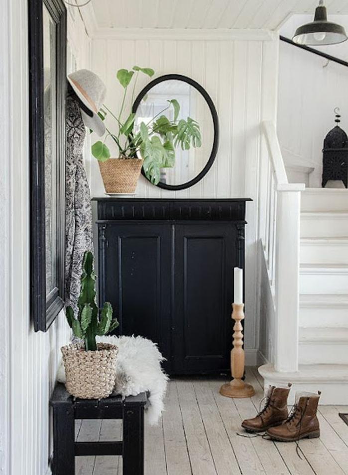 exemple de hall entrée maison, meuble chaussures noir, parquet clair, miroir ovale et grand miroir rectangulaire, plante verte, lambris blanc