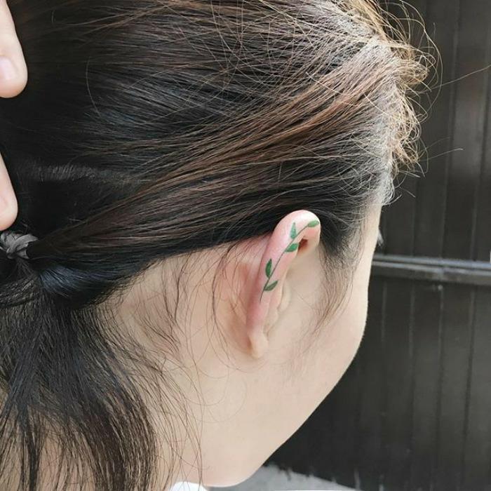 Formidable tatouage plume derriere oreille pour femme