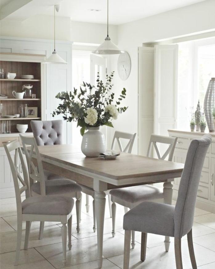 deco campagne chic dans la salle à manger, table en bois, chaises en bois blanches avec revêtement gris, vase de fleurs, vaisselier blanc, suspensions