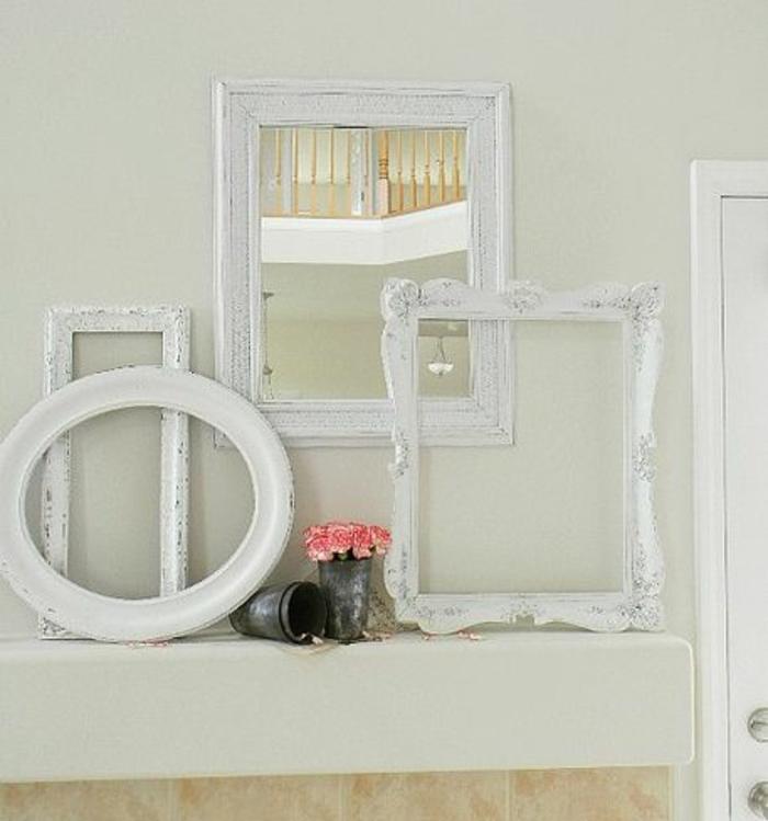 comment décorer un mur, cadres vides blancs et miroir, bouquet de fleurs dans un vase vintage, idee deco salle de bain