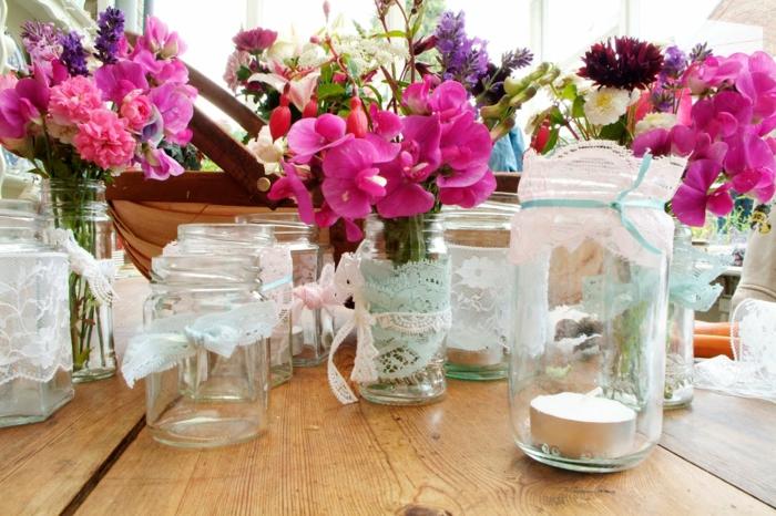 idee deco mariage, des pots en verre customisés de dentelle, bougeoirs et pots de fleurs, remplis de bouquets