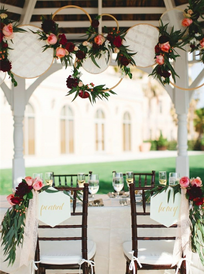 idee deco mariage champetre chic, des tambours à broder en dentelle, guirlande de fleurs, chaise en bois, nappe blanche, decoration florale