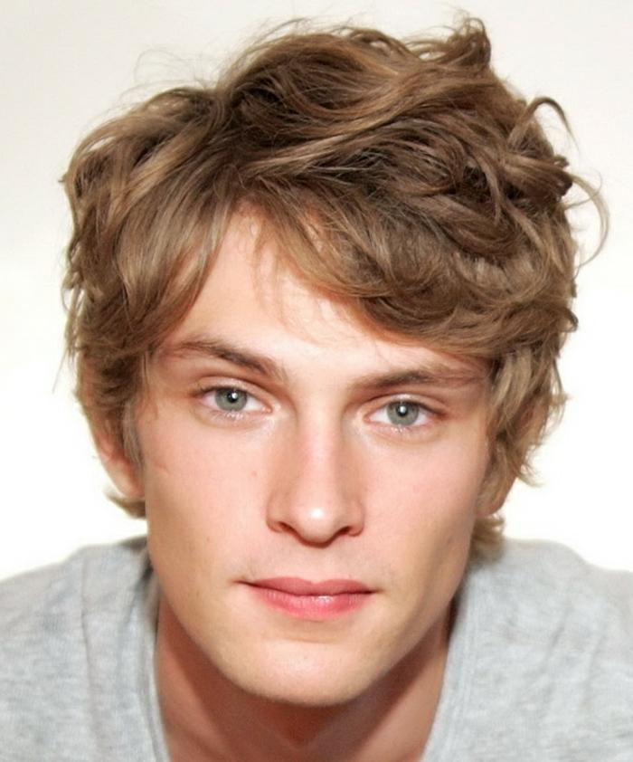 coiffure ado garçon type shag, des mèches tombant sur le front, garcon blond, cheveux bouclés et des yeux verts