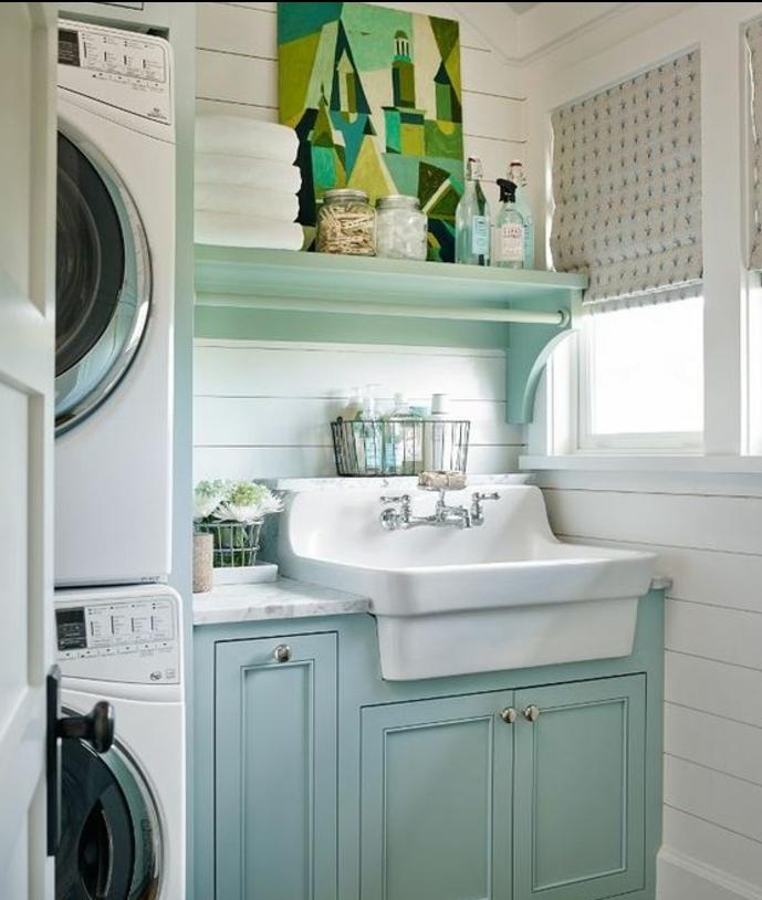 idee comment amenager une buanderie, vasque blanche et meuble sous vasque bleu pastel, tableau peinture decoratif vert, machines à laver