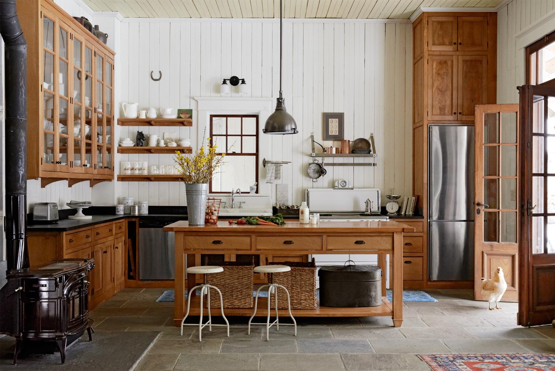 modèle de cuisine campagne chic, ilot central en bois et façade cuisine en bois marron, lambris blanc, revêtement sol de carreaux de ciment, vaisselle blanche, vaisselier en bois, suspension industrielle