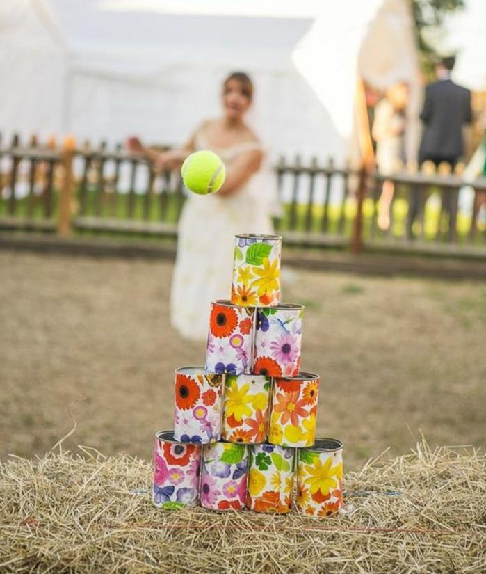 idée pour organiser un jeu de mariage avec des boites de conserve customisées à motifs floraux et balle de tennis, idée mariage champetre chic