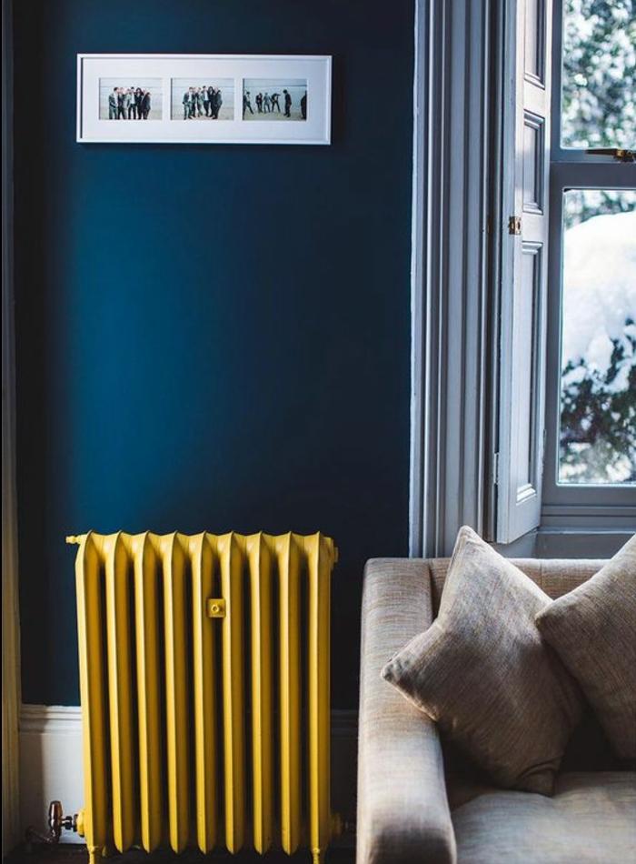 deco bleu et jaune, un radiateur repeint en jaune pastel, canapé gris et mur couleur bleu foncé, decoration murale de photos