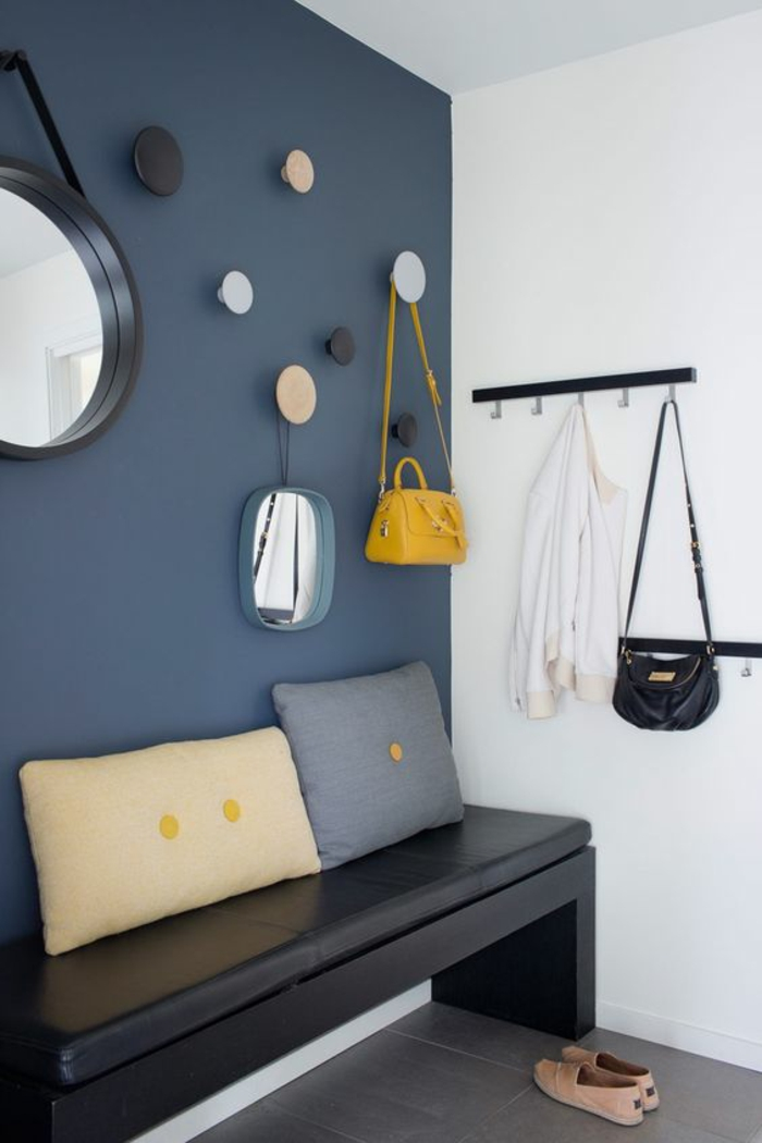 hall d'entrée maison avec mur en bleu pétrole et suspensions rondes multicolores et banc noir tapissé