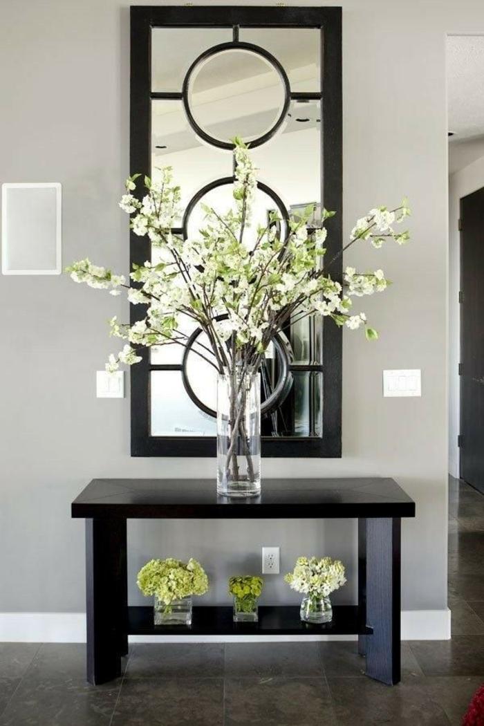 hall entrée maison avec miroir long aux cercles décoratifs et table basse en noir