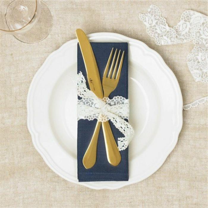 idée décoration mariage, une serviette bleu marin, couverts serrés de bande en dentelle blanche, deco table