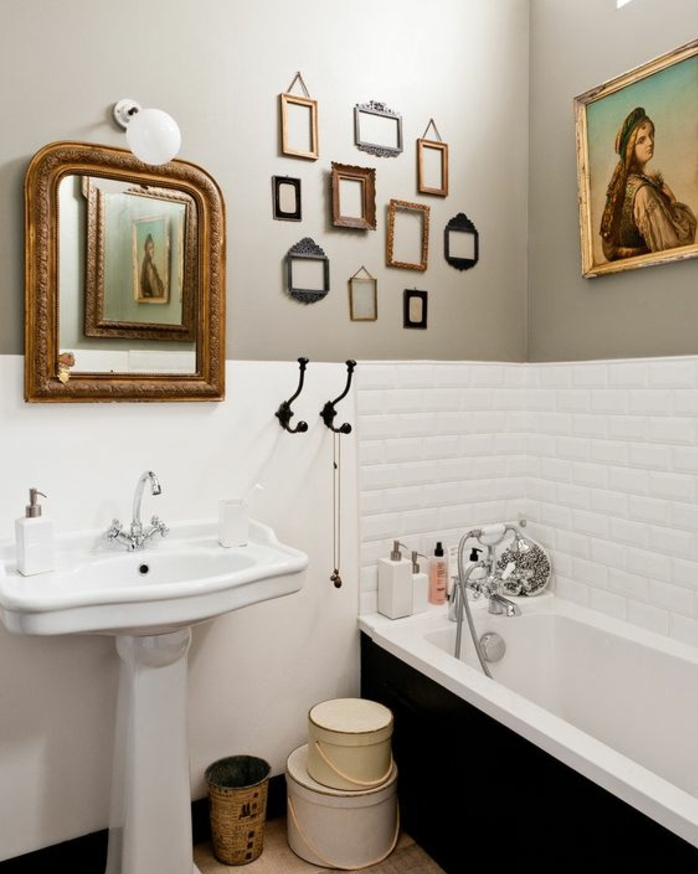 salle de bain en blanc et gris, carrelage blanc, lavabo colonne, miroir vintage, baignoire encastrée, deco cadre vide, plusieurs petits cadres photo retro