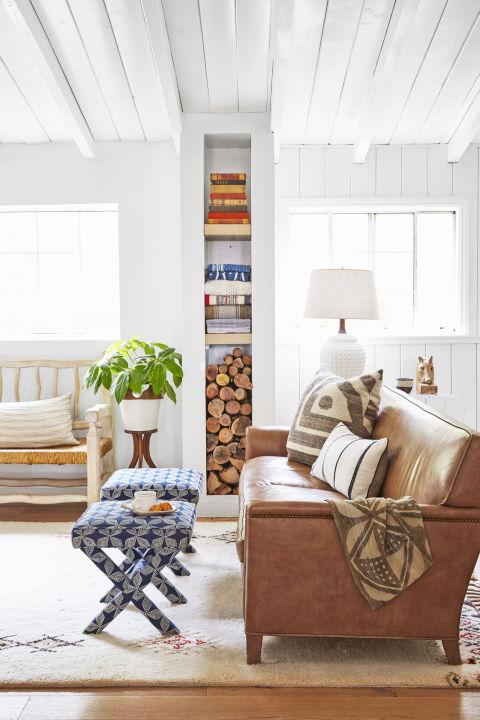 exemple de deco sejour campagne chic, canapé en cuir marron, tapis blanc à motifs géométriques, colonne de rangement, bois livres, serviettes, banc en bois, tabourets en bleu et blanc