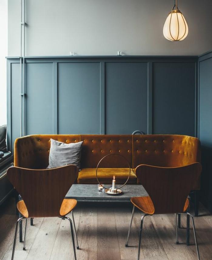 interieur vintage industriel, deco bleu et jaune, canapé jaune moutarde, chaises en bois et métal, table basse, mur couleur bleu gris, parquet en bois brut, suspension industrielle