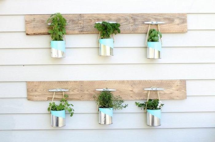 recyclage boite de conserve, boites pleins de fines herbes et accrochés sur des planches en bois, deco exterieure