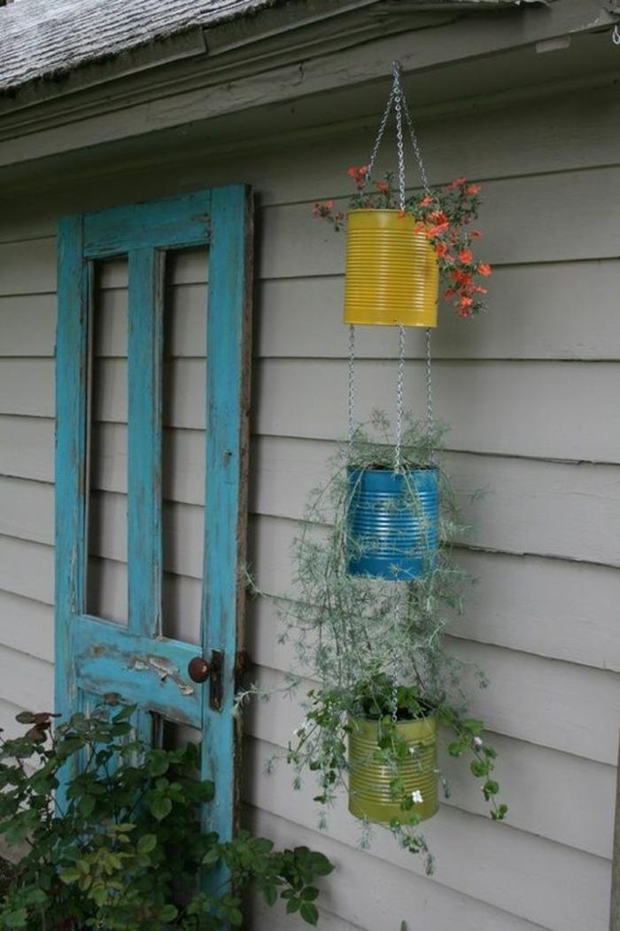 grosse boite de conserve pour fabriquer une jardiniere exterieure à trois niveaux, peindre boite de conserve de couleurs diverses et créer un cache pot diy