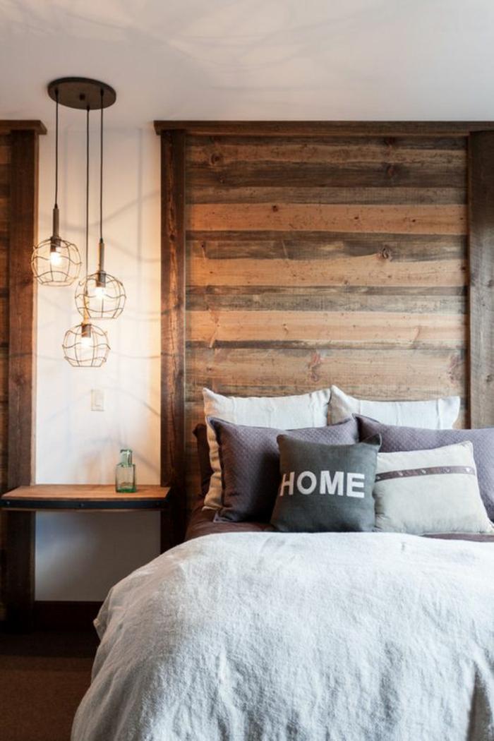 une chambre à coucher rustique moderne à tête de lit en bois, un luminaire suspension à trois lampes