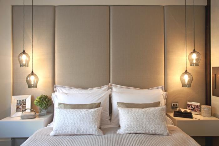une chambre à coucher aux tons neutres au décor harmonieux, un luminaire suspension bas en verre de chaque côté du lit