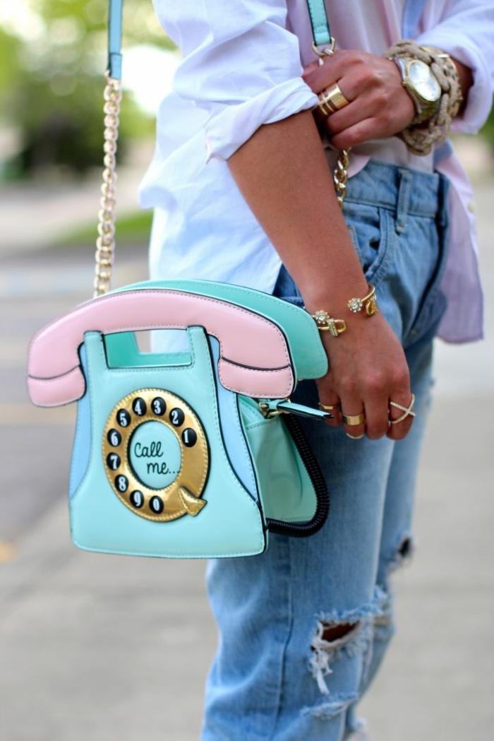 look des annees 80 denim bleu clair déchiré aux genoux et sac en forme de rétro téléphone aux nuances pastel